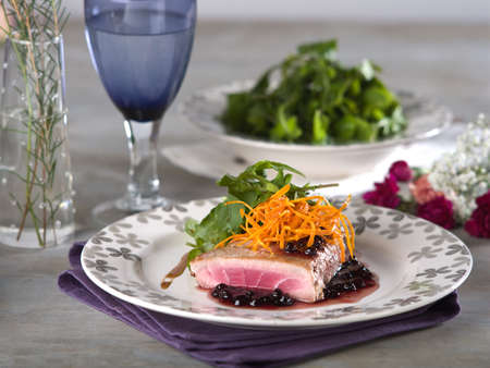 Tuna steak in blackberry sauce served on white plate in fine dining setting