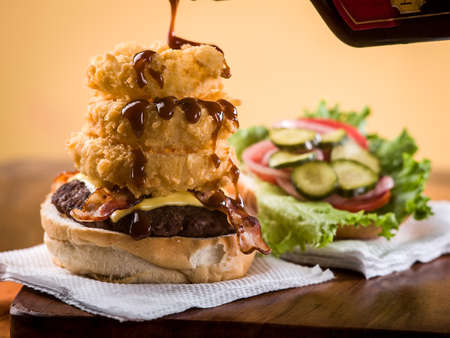 Bacon cheeseburger with stack of onion rings sitting on a paper napkin on wooden table top Stock Photo