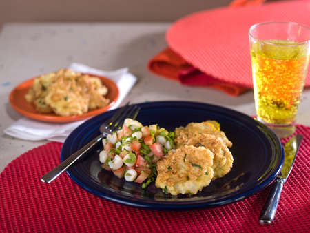 Fried cauliflower, torrejas de coliflor, a typical Peruvian dish served on blue plate on red place mat Stock Photo