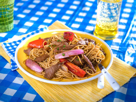 Beef and noodle stir fry, Tallarin saltado, a typical Peruvian dish served in yellow bowl on blue and yellow checked table cloth Stock Photo - 56406614