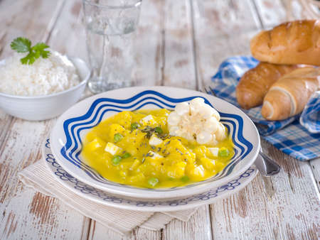 Squash stew, Locro de zapallo, a typical Peruvian dish served in white and blue bowl on white wooden table top Stock Photo - 56406623