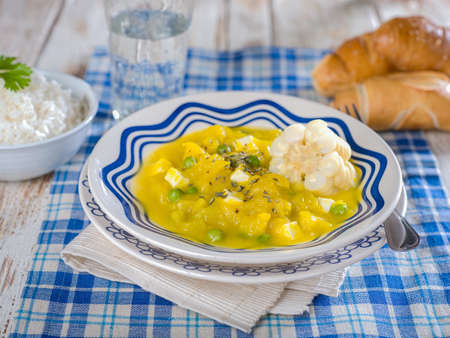 Squash stew, Locro de zapallo, a typical Peruvian dish served in white and blue bowl on blue plaid place mat on white wooden table top
