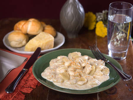Potato Gnocchi in creamy Alfredo sauce on green ceramic plate on wooden table top Stock Photo