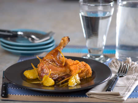 Duck a La Orange on dark ceramic plate on blue toned place mat Stock Photo - 56403090