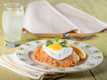 Tacu tacu, re-fried beans and rice, a typical Peruvian dish on light colored plate sitting on light green wooden tabel top Stock Photo