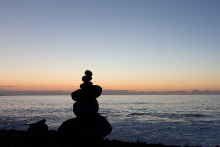 nger: Beach sunset with stacked stone pyramid