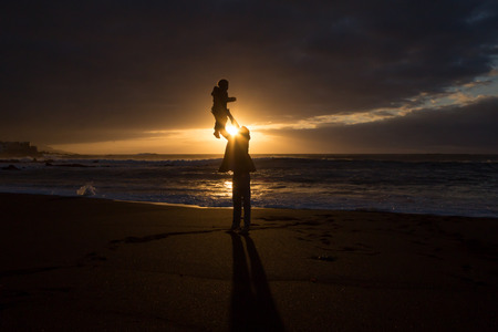 ensuring: Father and child - family silhouette sunset -Beach Stock Photo