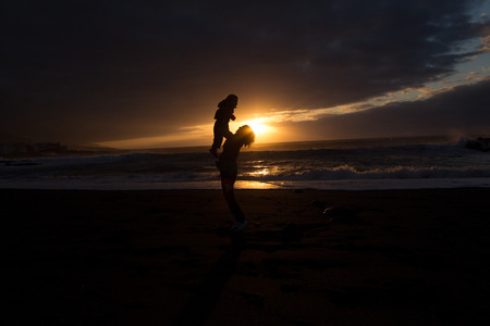 ensuring: Mother and Child - Family silhouette Sunset -Beach