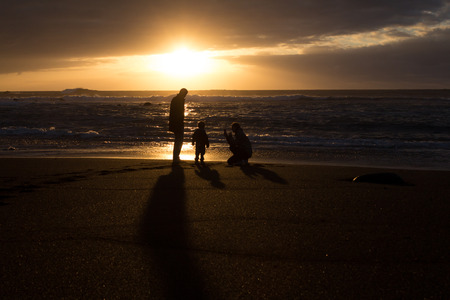 ensuring: Parents and child - family silhouette - sunset at beach
