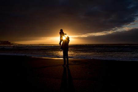 ensuring: Father and child - family silhouette - sunset at beach Stock Photo