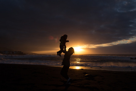 parental love: Mother and child - family silhouette - sunset at beach
