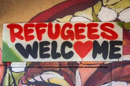 Vluchtelingen verwelkomen graffiti teken Stockfoto