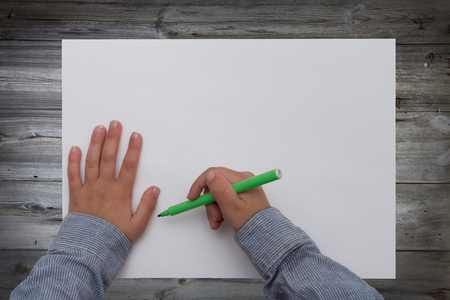 hoja en blanco: ni�o que sostiene la pluma en la hoja de papel en blanco