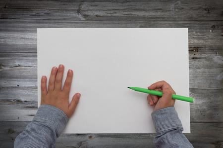 hoja en blanco: niño que sostiene la pluma en la hoja de papel en blanco. las manos del niño de dibujo en el escritorio