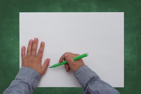 hoja en blanco: niño que sostiene la pluma en la hoja de papel en blanco