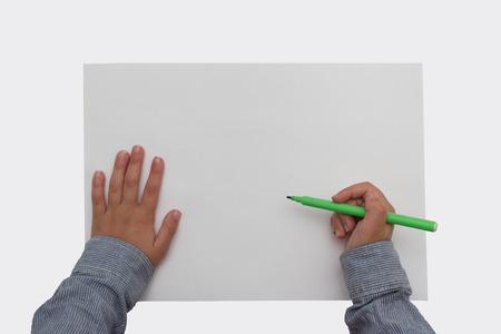 hoja en blanco: que sostiene la pluma en la hoja de papel en blanco niño - escritorio blanco