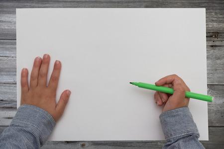 blank sheet: ni�o que sostiene la pluma en la hoja de papel en blanco