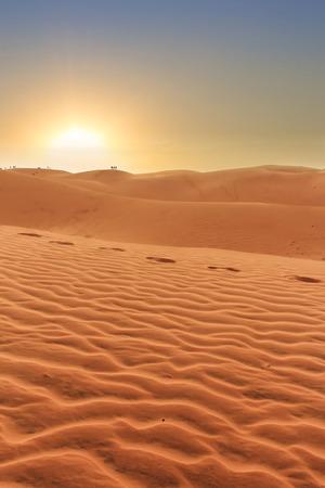 puesta de sol: paisaje del desierto, puesta del sol detr�s de las dunas de arena, siluetas de personas en el fondo y las huellas en la arena Foto de archivo