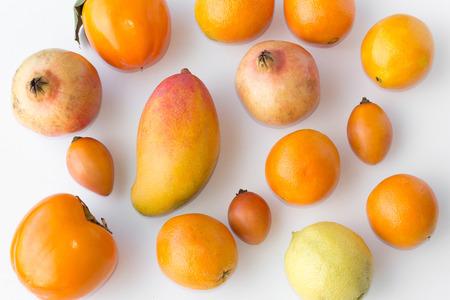 Many fresh orange fruits on white background - orange, mango, lemon, kaki