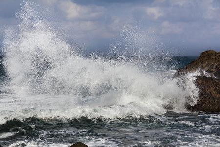 granola: gran ola salpicaduras sobre la roca - olas rompiendo en la orilla Foto de archivo