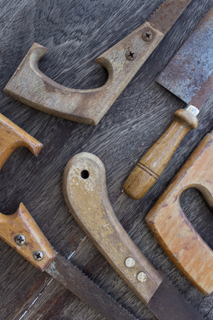 splitting up: wooden handles of old saws Handsaws old details on wooden background