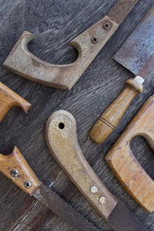 splitting up: wooden handles of old saws Handsaws old details on wooden background