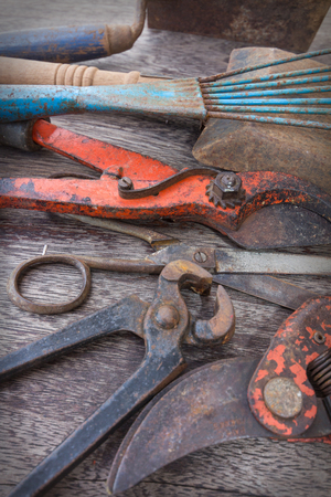 Old rusty tools - vintage handicraft tools on wooden background