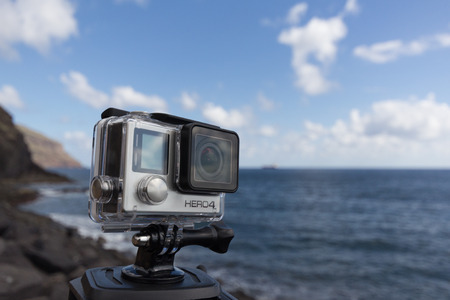Tenerife, Spain - Nov 17, 2015: Shot of GoPro Hero 4 Black on tripod with ocean background. It is a compact, lightweight personal camera manufactured by GoPro Inc.