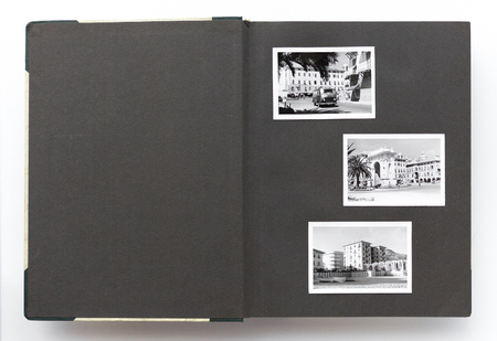 Open vintage photo album with blank page and old black and white photos
