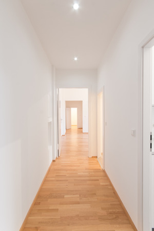 fresh renovated flat corridor, white walls, wooden floor.