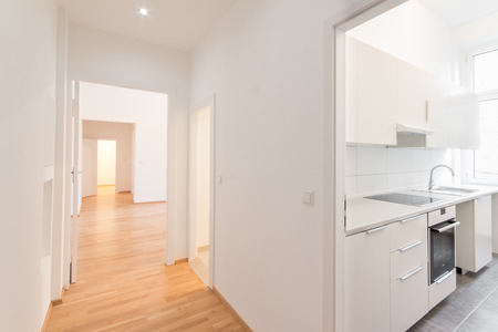 fresh renovated flat - home apartment - renovated flat, corridor and kitchen, white walls and wooden floor Stock Photo