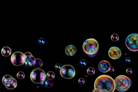 balance rainbow colors: many colorful soap bubbles on black background with copy space