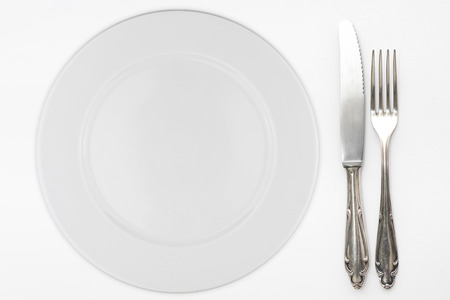 empty plate with beautiful silver knife and fork on white background Standard-Bild