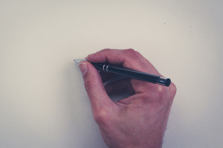 blank page: hand holding pen isolated over white background - hand holding pencil on white paper Stock Photo