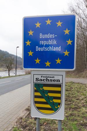 the entering: german border street sign, saxony emblem - entering germany Stock Photo