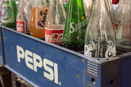 business rival: Phnom Penh, Cambodia- January 02, 2014. Coca-Cola bottles in Pepsi container - vintage style. Symbolic representation of one of the greatest business rival manufacturers of all time.