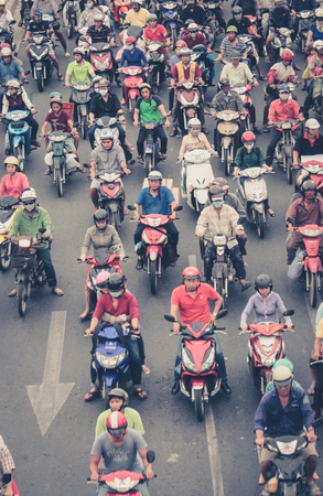 multiples: Saigon, Vietnam, January 18. 2014: Road traffic crowded with motorbikes and scooter drivers. Motorbikes are the most favorite vehicles in saigon. Editorial