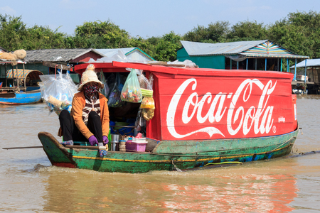 tonle sap: Tonle sap lake near Siem Reap, Cambodia, January 10, 2014: Coca Cola logo painted on wooden boat, floating village, Cambodia. Coca cola is probably the worlds most famous brand.