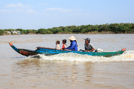 siem reap: Tonle sap lake near Siem Reap, Cambodia, January 14, 2014: Family on boat near floating village on tonle sap lake , near siem reap, cambodia.