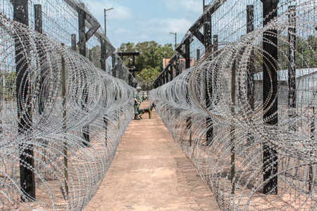 locked up in a cage: barb wire fence. guarded border Stock Photo
