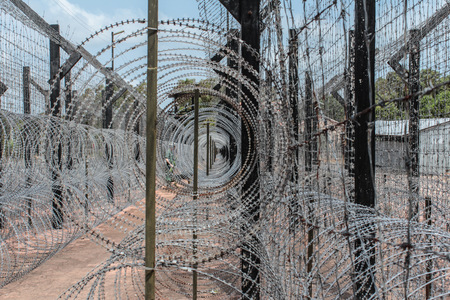 locked up in a cage: barbwire fence. guarded border Stock Photo