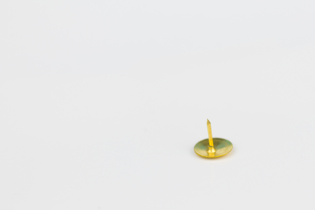 inconvenient: one thumbtack  isolated on white background with copy space