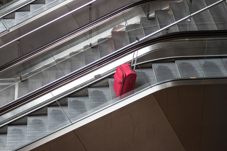 unattended: red rolling suitcase on escalator traveling alone