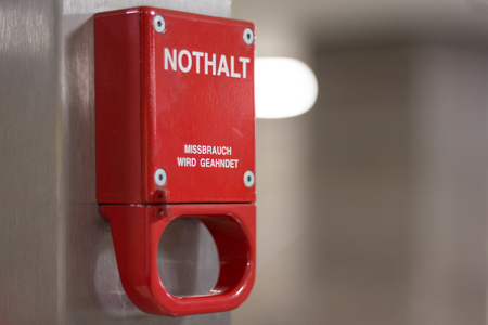 punishable: Berlin, Germany - march 30, 2016: Red emergency brake marked with german words Nothalt Missbrauch Strafbar (Emergency brake, misuse punishable) in underground metro station.