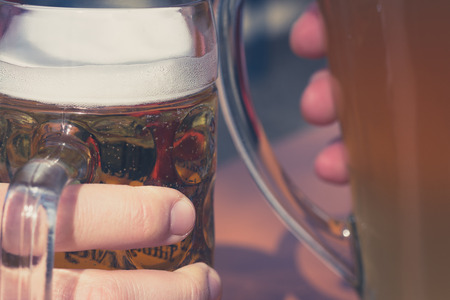 clink: drinking beer in beer garden concept - clink glasses closeup