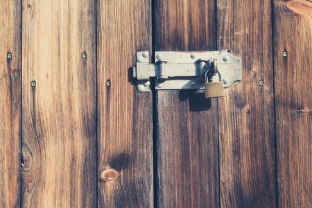 vintage look: old wooden door with padlock and metal latch - vintage look