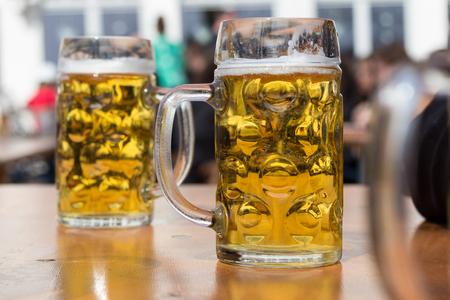 two beer glasses in german beer garden background