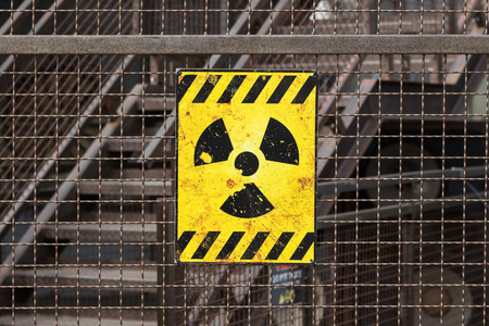 rusty fence: yellow radioactive warning sign on rusty fence