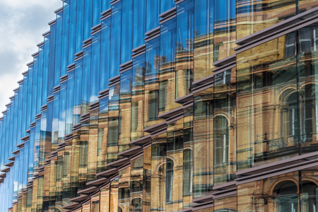 property development: old building facade reflection in modern building glass facade Editorial