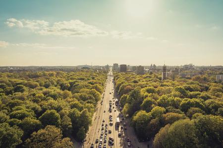 도시의 스카이 라인과 푸른 하늘이 숲을 통과하는 도로 스톡 콘텐츠